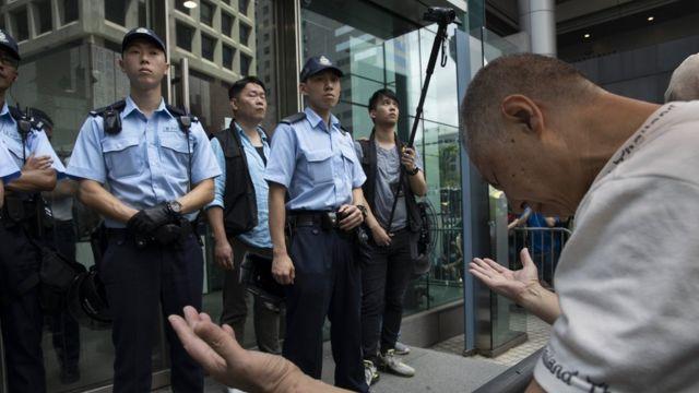 便裝警員在一列軍裝警員身後舉起攝錄機拍攝示威者(21/6/2019)
