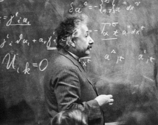 Einstein en 1931 dando clase frente a una pizarra llena de ecuaciones.