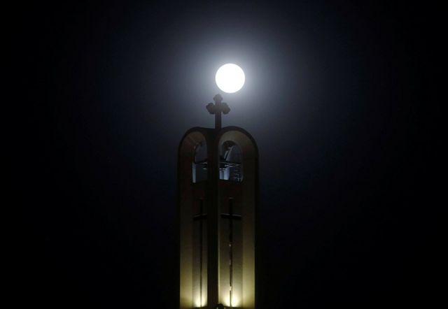 The moon rises behind The cross of St Antony Church