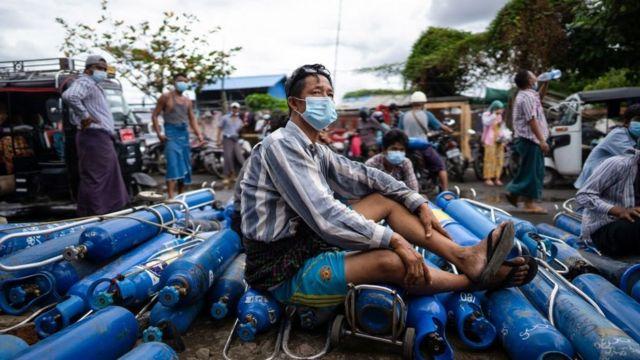 Seorang warga duduk di atas tabung oksigen di Mandalay