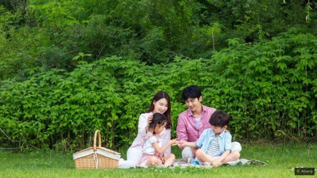 Casal e dois filhos, uma menina e um menino, fazendo picnic em jardim