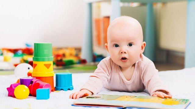 Bebé con un libro y juguetes.
