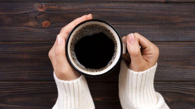 Una joven tiene entre sus manos una taza de café