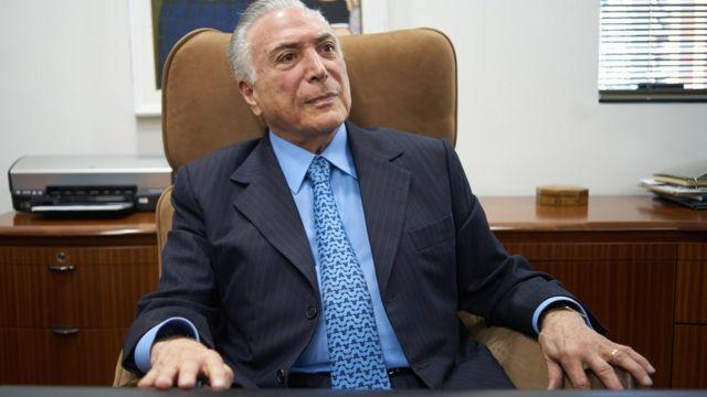 Bolsonaro olha para cima sentado na poltrona de seu escritório