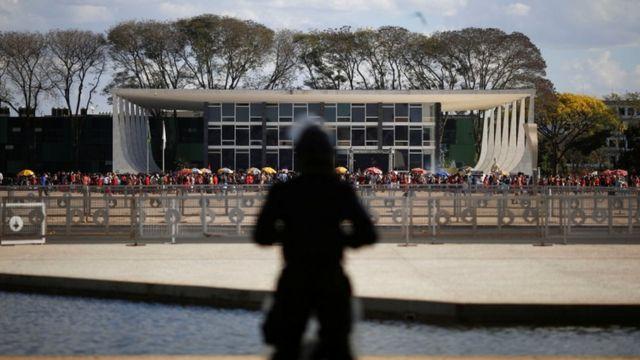 Sombra de guarda em frente a prédio do STF, com vários manifestantes em frente