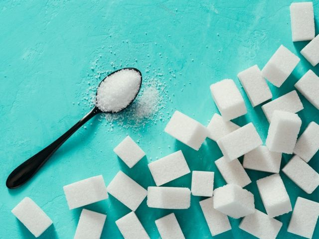 Vista de cubos de azúcar sobre fondo turquesa.