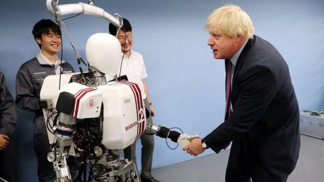 约翰逊在访问日本时和机器人互动