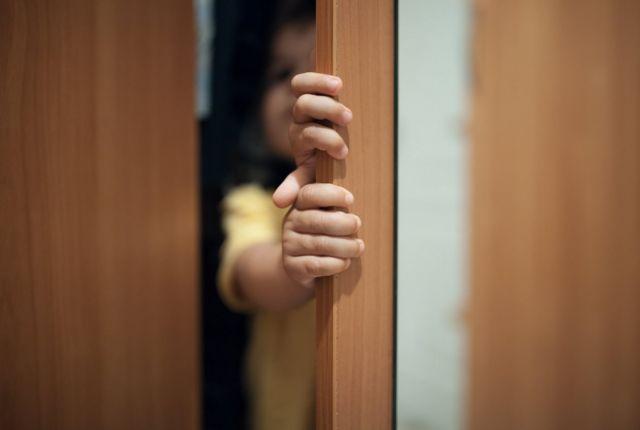 Criança atrás de porta