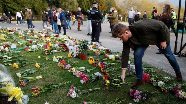 شخص يضع باقة من الزهور خارج قلعة ويندسور