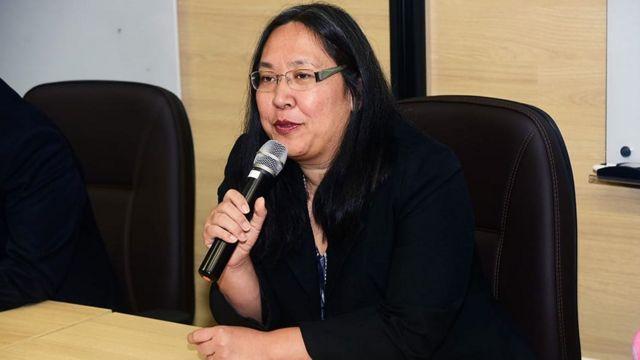 A pesquisadora Marisa Beppu fala no microfone, sentada diante de mesa em sala
