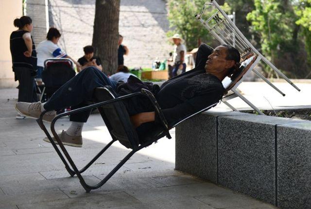 Un hombre chino se echa la siesta en un parque