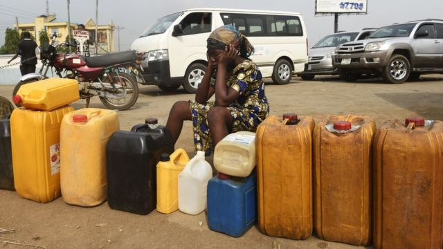 Woman siddon with jerry can for petrol station
