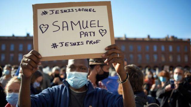 """Un hombre en una manifestación en Francia con un cartel que dice """"Yo soy Samuel"""", """"Yo soy profesor""""."""