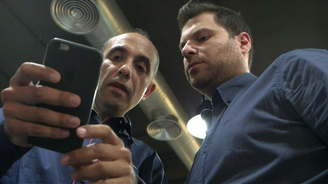 The founders of Anghami looking at a phone
