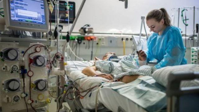 Médica e paciente em cama de hospital