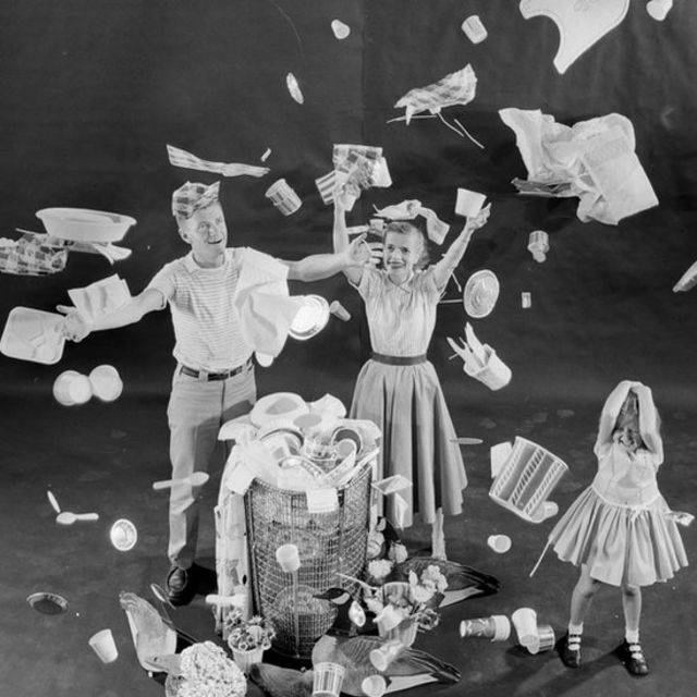 Familia feliz llenando la caneca de basura con productos desechables.