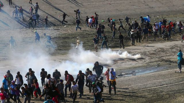 Migrants run from tear gas, thrown by the US border patrol, near the border fence between Mexico and the United States in Tijuana, Mexico, November 25, 2018