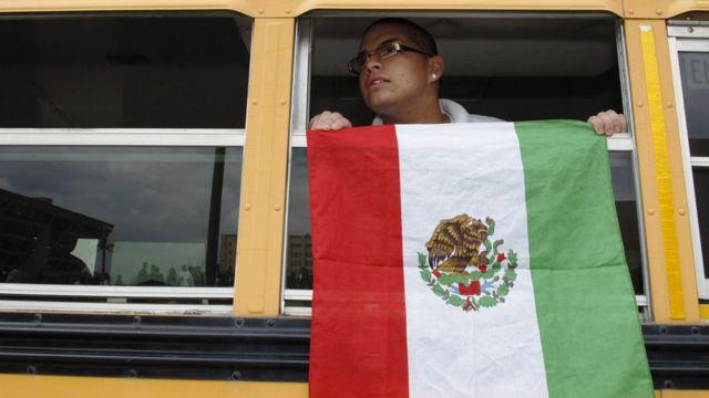 Un alumno despliega una bandera de México en un autobús escolar en Texas, EE.UU.