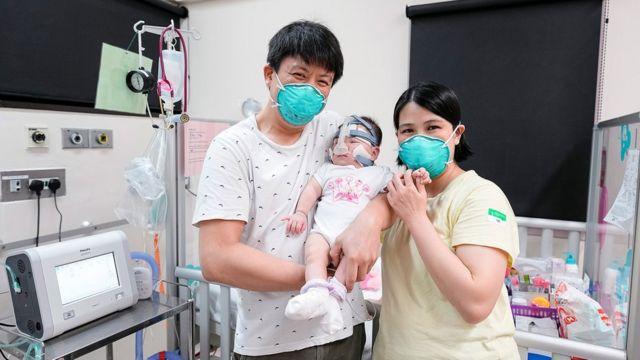 Kwek Yu Xuan com seus pais antes de receber alta do hospital