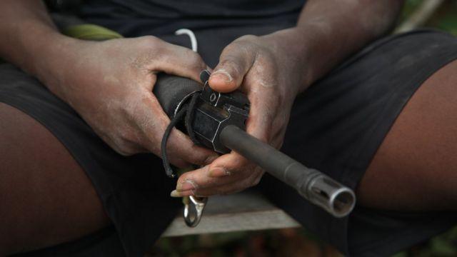 Un guerrillero sostiene un fusil en sus manos.