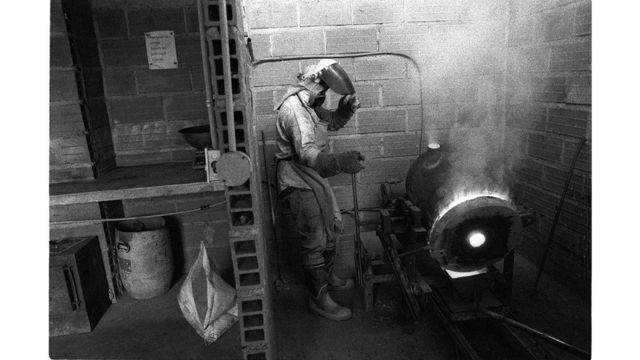 Hombre trabajando el oro en un horno.
