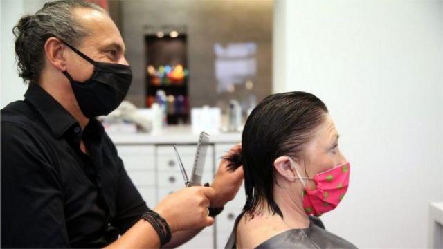 Cabeleireiro atende cliente, ambos usam máscaras de proteção contra a covid-19