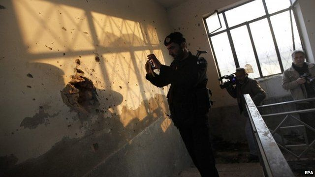 Pakistani security official takes pictures of a bullet-ridden wall