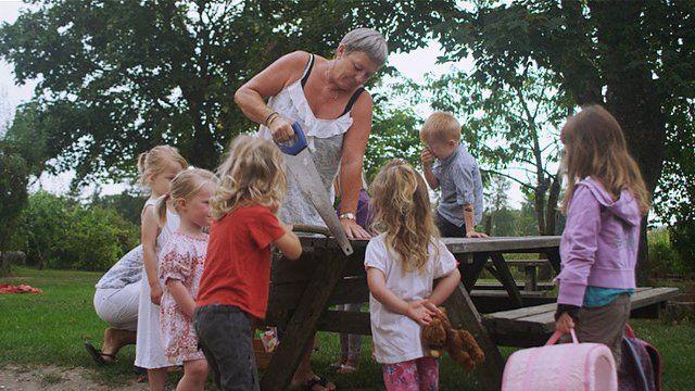 """Pedagoga mostra a crianças como serrar madeira em cena do documentário """"Nature Play"""""""