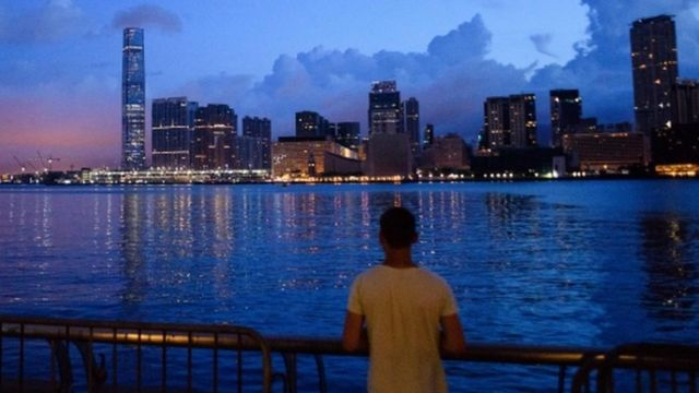 A man looks on as light pollution illuminates clouds above the Kowloon skyline in Hong Kong before sunrise on June 26, 2017.