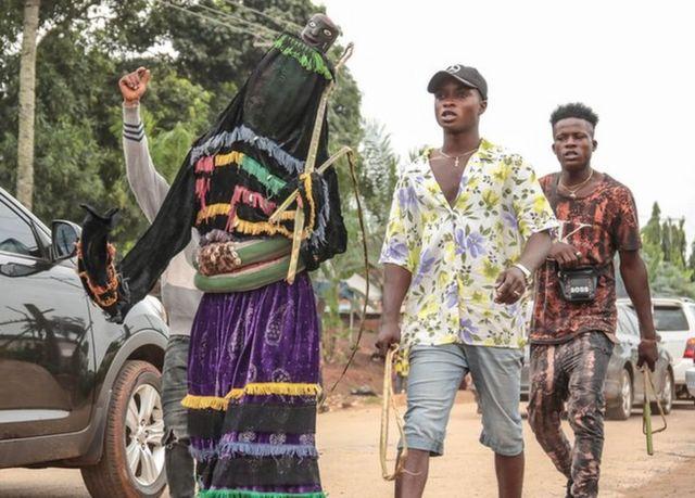 Kundi la watu waliovalia vinyago wakitembea kwenye mitaa ya Arondizuoguwakati wa tamasha la Ikeji nchini Nigeria