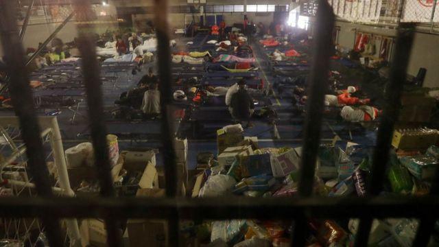 Pessoas se preparam para passar a noite em ginásio