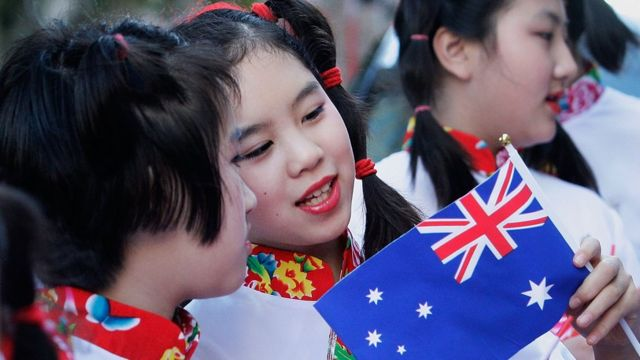 A girl in a traditional Chinese outfit talks to her friend and carries a small Australian flag as she prepares to join a festive parade