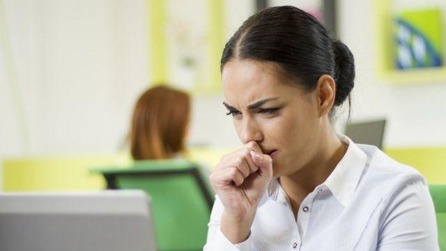 Mujer tose frente a la computadora.