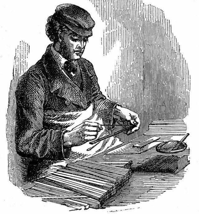 Un hombre inserta grafito entre palos de madera de cedro en un grabado de 1872.
