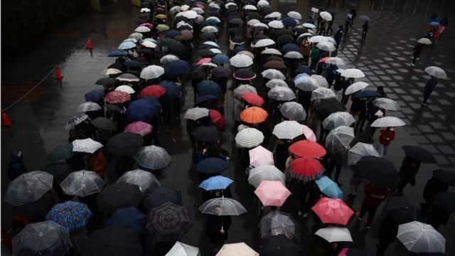 People queue in the rain outside a court in Yokohama on January 8, 2020, to attend the trial of Satoshi Uematsu