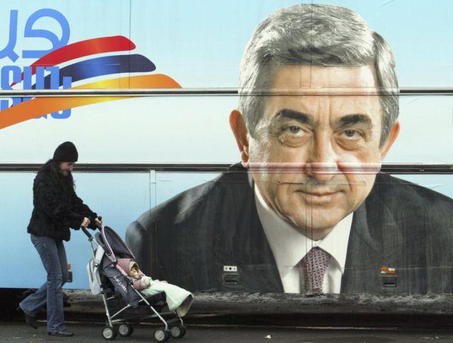 Женщина с коляской на фоне предвыборного плаката