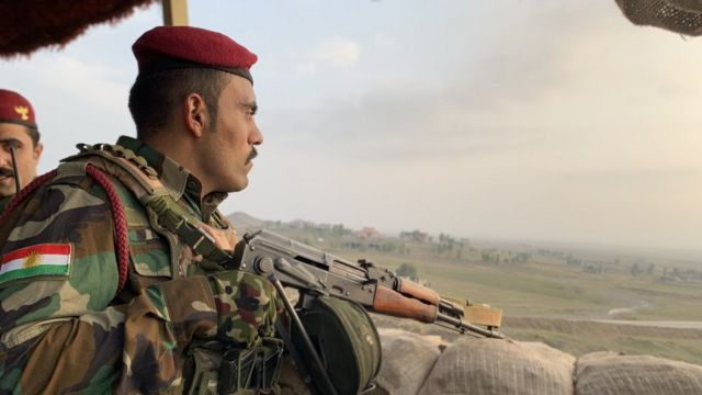 Peshmerga fighter looks out across no man's land