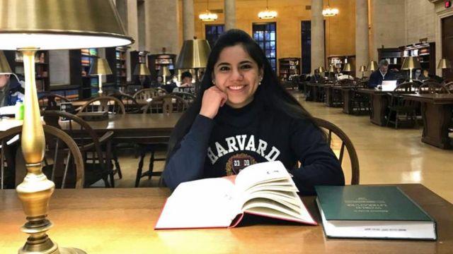 Dafne Almazán sentada em uma biblioteca com um moletom onde lê-se Harvard. Jovem de 17 anos foi aceita no curso de matemática da instituição