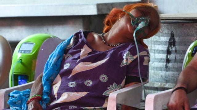 A woman receives oxygen via a mask