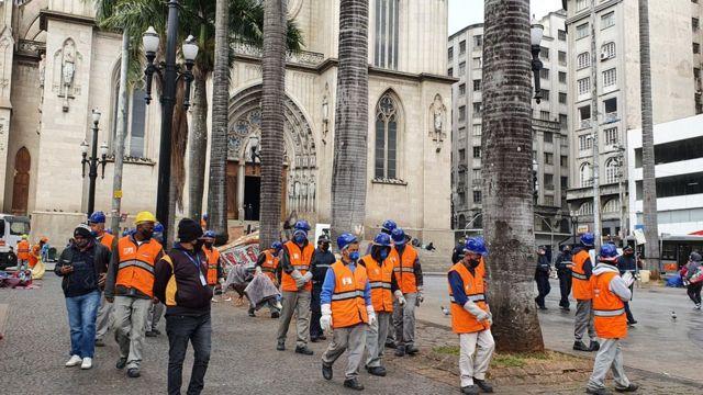 Equipes da prefeitura são protegidas por guardas municipais enquanto fazem limpeza na praça da Sé