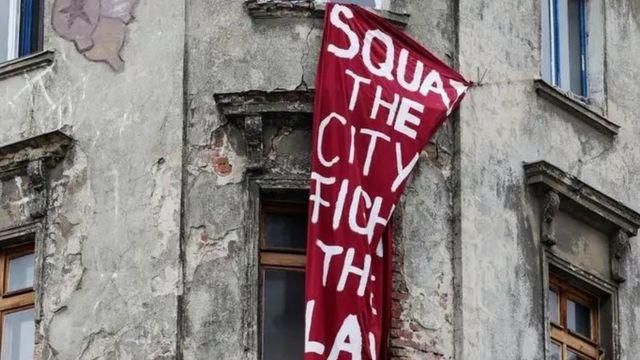 """Berlin'de bir eve asılan """"Kente izinsiz yerleşin"""" başlıklı bir pankart"""