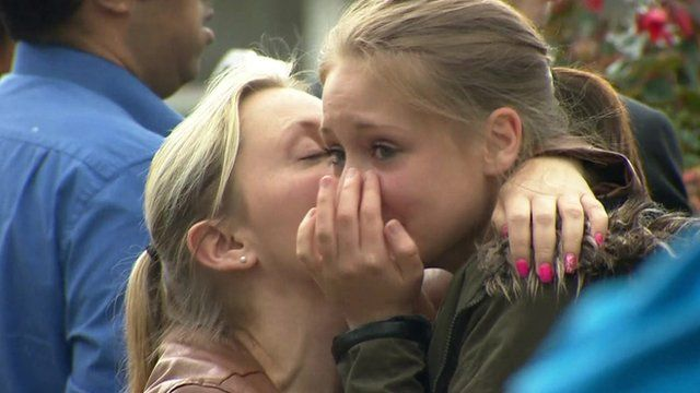 A young woman is comforted at a memorial for Jo Cox