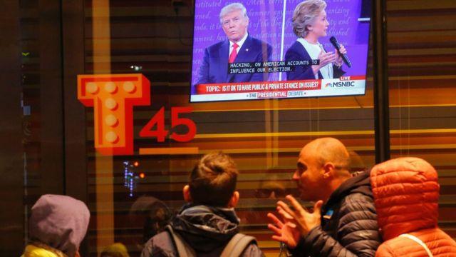 न्यूयार्क के टाइम्स स्कवॉयर पर डोनल्ड ट्रंप और हिलरी क्लिंटन की बहस को देखते लोग.