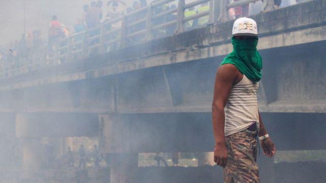 Manifestante con la cara tapada en medio de gases