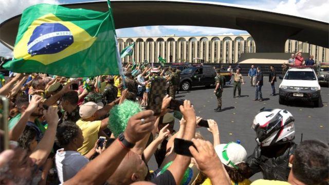 Dezenas de pessoas tiram fotos, levantam cartazes e bandeiras diante de Bolsonaro, que acena de cima de carro em área externa de Brasília
