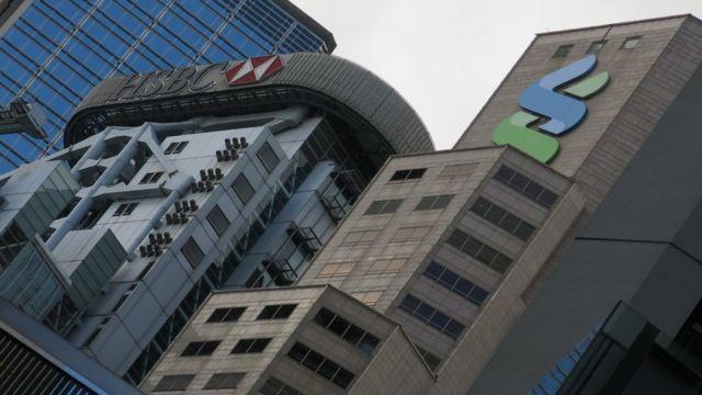 汇丰银行香港总行大楼(左)与香港渣打银行大厦(右)(资料图片)