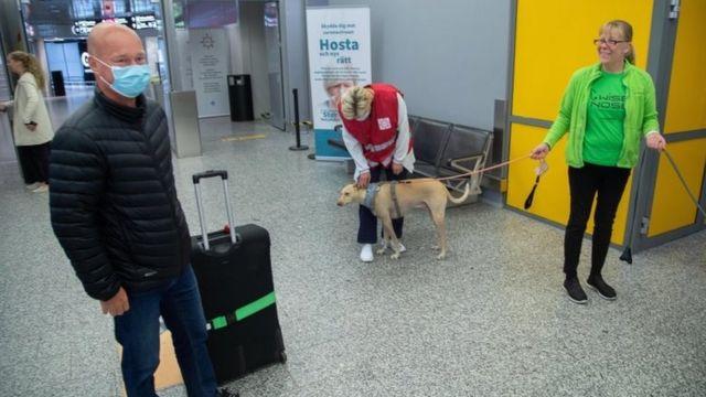 Un pasajero (izquierda) se prepara para ser examinado por el perro rastreador Kossi.