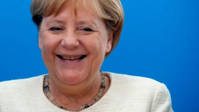 Merkel sonríe.
