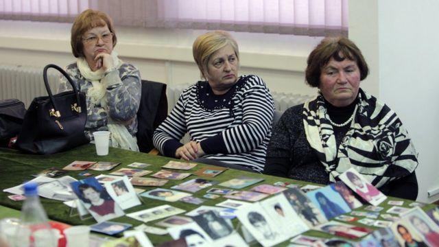 犠牲者の写真を前に判決読み上げの中継を見守るサラエボの女性たち(24日)