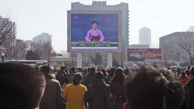 ロケット発射の発表を大型スクリーンで見る平壌の人たち(7日)